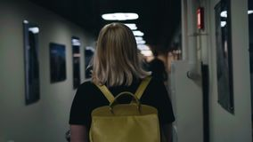 The girl goes down a long corridor with lamps on the ceiling. Cool footage. stock video
