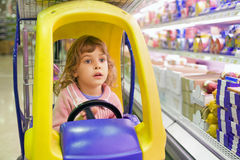Girl goes for drive on shoppingcarts in market Stock Image