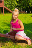 Girl goes for a drive on a swing. Girl riding a wooden swing in the park stock photos