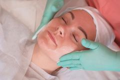 The girl goes through facial treatments in the beauty salon. Beautician wearing gloves apply moisturizer on the woman`s face. royalty free stock photo