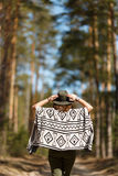 The girl goes on a forest alley dressed in Indian poncho. Stock Image