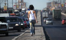 Girl goes on highway middle in city Stock Photography
