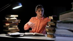 Girl goes through a lot of books and can not find the desired information. Black background stock footage