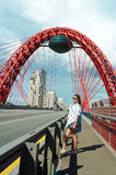 The girl goes over the bridge along the road with cars passing by Stock Photo