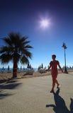 Girl goes on path with palms on empty sandy beach Stock Photos