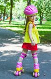 Girl goes rollerblading in the park Royalty Free Stock Image