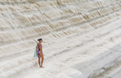 """The girl goes on a slope of white cliff called """"Scala dei Turchi"""" Royalty Free Stock Images"""