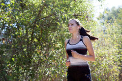 Girl goes in for sports runs in forest Royalty Free Stock Photography
