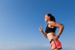 Girl goes in for sports runs and listens to music Royalty Free Stock Images