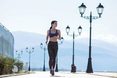The girl goes in for sports, runs in the morning along the promenade by the sea Royalty Free Stock Photos