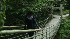 Girl goes on a suspension bridge in a dense forest stock video