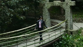 Girl goes on a suspension bridge in a dense forest stock footage