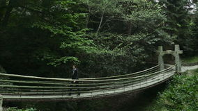 Girl goes on a suspension bridge in a dense forest stock video footage