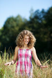 Girl Goes In Tall Grass At Park Royalty Free Stock Photography