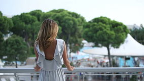 Girl goes to the balcony in front of her hotel offers beautiful views stock video footage