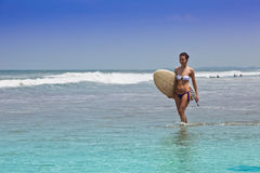 Girl goes to bikini on an ocean coast with a board for surf Stock Image