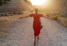 Girl goes to meet a bright sun near the ramparts Stock Photography