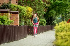 Girl goes to school on a scooter Stock Image