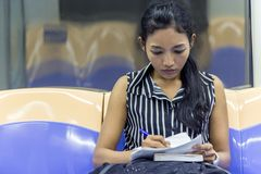 Girl goes by train and studying her notes. Royalty Free Stock Photo