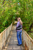 Girl goes on a wooden bridge and turns Stock Photos