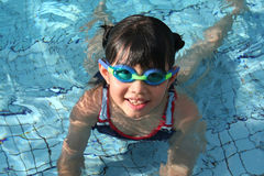 Girl with goggle in the pool. On sunny day stock photo