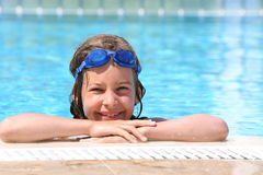 Girl in goggles on forehead swimming in pool Royalty Free Stock Images