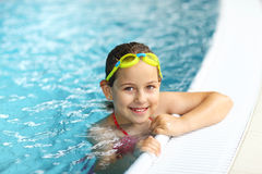 Girl with goggles in swimming pool. Cute girl with goggles in swimming pool Royalty Free Stock Image