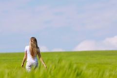 Girl going away in green field Royalty Free Stock Photo