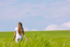 Girl going away in green field. Young girl going away in green field Royalty Free Stock Photo