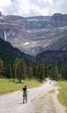 Youth hiker on the way to the cirque of Gavarnie in Pyrenees. A girl is going on the hiking trail to falls of the cirque of Gavarnie. In the background there is royalty free stock photography
