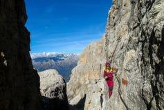 Girl going the mountain via ferrata in Dolomite Alps
