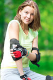 Girl going rollerblading sitting in bench putting on elbow guard Stock Images