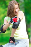 Girl going rollerblading sitting in bench putting on elbow guard Stock Photos