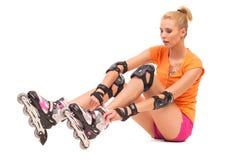 Girl going rollerblading sitting on the floor. Stock Image