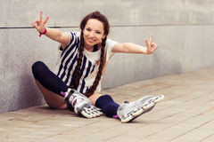 Girl going rollerblading sitting putting on inline skates Royalty Free Stock Photography