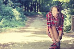 Girl going rollerblading sitting putting on in line skates outdoors Royalty Free Stock Images