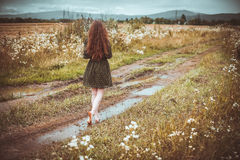Girl going on rural road Stock Photos