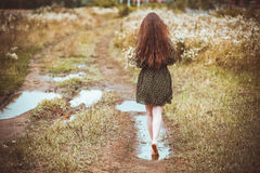 Girl going on rural road Stock Images