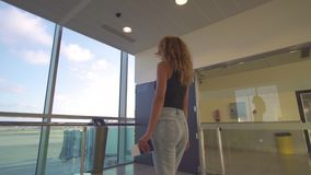 Girl going to the airplaine, go in the terminal at the airport, holding passport and ticket. stock video footage