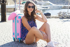 Girl going to cruise with pink suitcase Stock Images