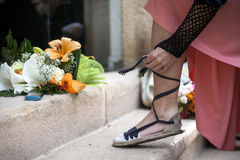 Girl is Going to the Party. Girl ties the laces on sandals and going to a party Stock Images