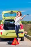 Girl is going to replace car wheel Stock Images