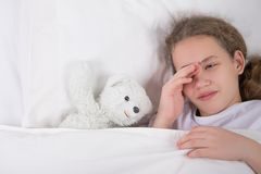 Girl is going to sleep, lies in bed next to a white teddy bear stock photo