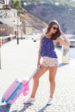 Girl going to vacations with pink suitcase. Pretty traveler girl is walking around quay with fashion pink suitcase and air cushion royalty free stock photography