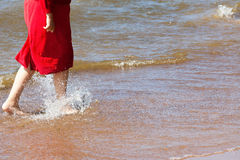 The girl going on water barefoot Stock Photography