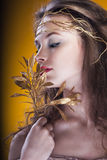 Girl with a gold branch in hair on yellow background Royalty Free Stock Image