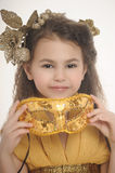 Girl in a gold with a carnival mask Stock Photo