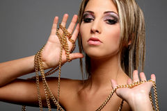 Girl with gold chain. Beautiful girl with gold chain isolated on gray background Royalty Free Stock Photos