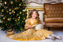 The girl in a gold dress on Christmas. The girl in a gold dress opens a Christmas and New Year's gift Royalty Free Stock Image