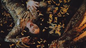 Girl in a gold dress with a red lipstick. Confetti falls stock video